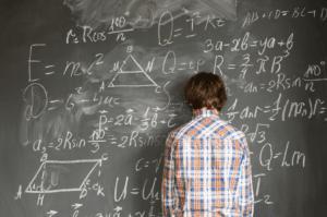 boy leaning on blackboard