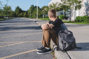 student sitting on kerb