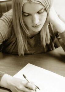 student writing her IA